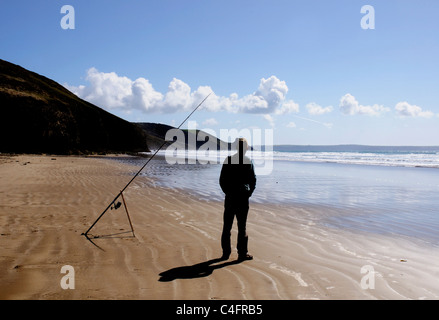 A sea fisherman by his fishing rod on Newgale beach in Pembrokeshire, Wales - Stock Photo