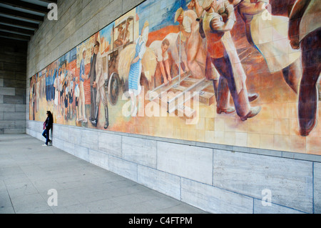 Socialist wall mural of happy workers on the wall of the Ministry of Finance building in ex East Berlin - Stock Photo