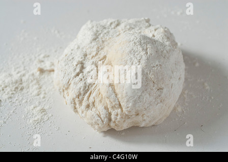 dough,ball,on,a,white,table,sprinkled,with,flour, - Stock Photo