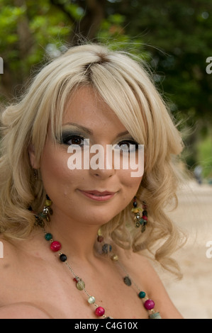 A young Maltese woman smiles for the camera while sitting outdoors in a garden - Stock Photo