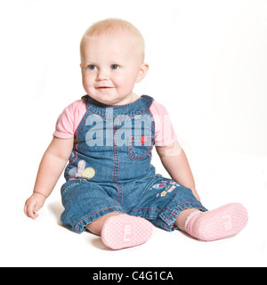 A cute 1 year old baby girl with blue eyes wearing denim and pink smiling against a pure white (255) background. - Stock Photo