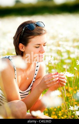 Girl smelling flower in field - Stock Photo