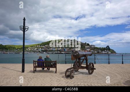 Middle-aged couple on seat and cannon, Dartmouth, South Devon England UK  United Kingdom GB British Isles - Stock Photo