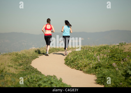 two athletic females, in workout clothes,  running on a dirt path through nature in the daytime - Stock Photo