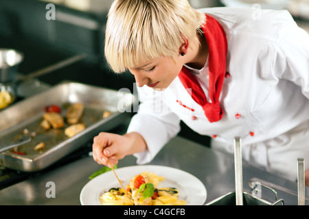 Female Chef in a restaurant or hotel kitchen cooking delicious food, she is finishing the dishes - Stock Photo