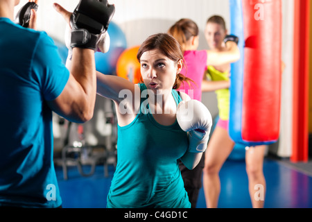 Woman Boxer hitting the sandbag, her trainer is assisting - Stock Photo