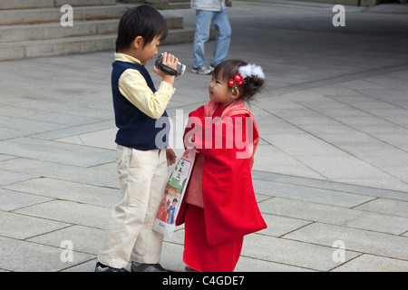 Big brother recording less-than-happy little sister dressed up for Shichi-Go-San (7-5-3) festival at Meiji-jingu - Stock Photo