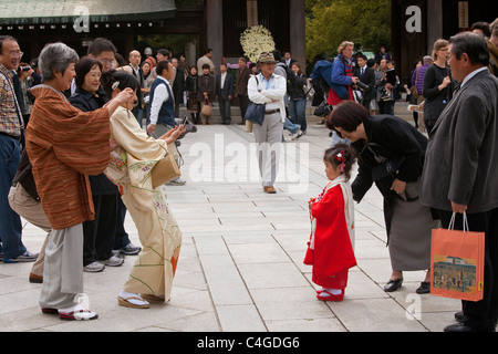 Family members take picture of three-year-old girl dressed up for Shichi-Go-San (7-5-3) celebration at Meiji-jingu - Stock Photo