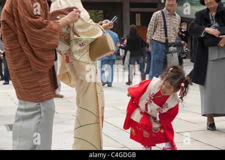 Mother and grandmother taking pictures of artful-dodger toddler dressed up for Shichi-Go-San (7-5-3) at Meiji-jingu, - Stock Photo