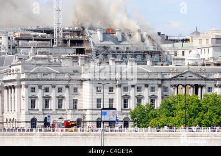 London fire brigade fire engine on way to Marconi House construction building site roof on fire Strand skyline seen - Stock Photo