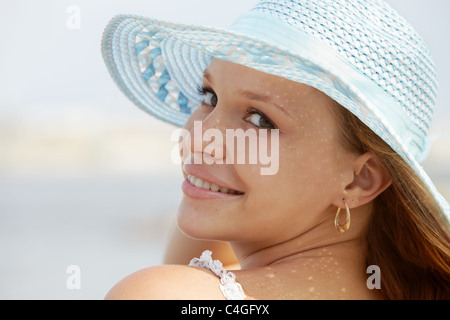 Beautiful happy young woman in straw hat smiling and looking over shoulders on the beach. Horizontal shape, copy space