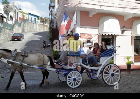 Santo Domingo Dominican Republic Ciudad Colonia Calle Hostos street scene horse carriage ride Black Hispanic man - Stock Photo