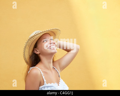 young adult blonde woman in straw hat laughing against yellow wall. Horizontal shape, side view, copy space - Stock Photo