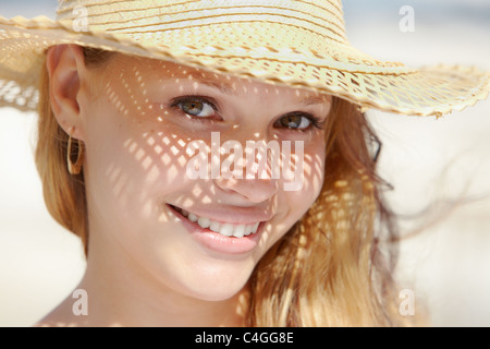 Beautiful happy young woman in straw hat smiling and looking at camera on the beach. Horizontal shape, headshot