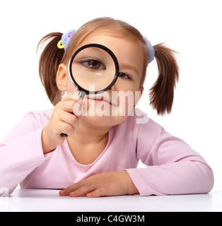 Curious little girl is looking through magnifying glass, isolated over white - Stock Photo
