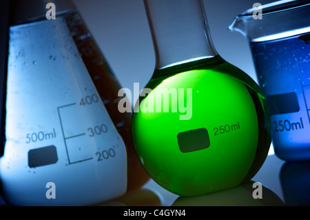 flask with liquid bright green and blue background - Stock Photo