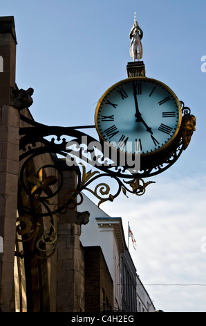 Clock mounred on a church wall in York City Centre, England. - Stock Photo