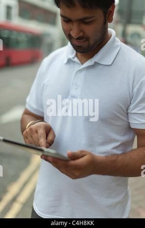Asian man using an Ipad 2 device on the street - Stock Photo