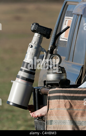 BBC's Big Cat Diary Photographer waits in Kenya's Maasai Mara, camera & telephoto lens rest on vehicle camera mount - Stock Photo