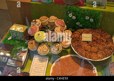 Display of cupcakes and florentines in a window in Bruges, Belgium. - Stock Photo