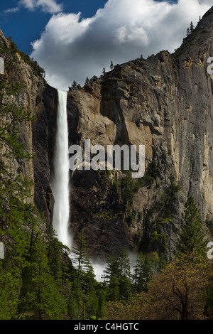 Yosemite National Park US waterfalls Bridal Veil Falls silky spring full flow, mist at base above trees, revealing - Stock Photo
