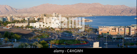 A 3 picture stitch panoramic view of the hotel and beach area of Eilat at sunset with Aqaba in the background. - Stock Photo