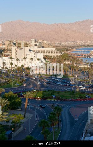 A vertical view of the hotel and beach area of Eilat at sunset with the city and coastline of Aqaba in the background. - Stock Photo