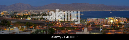 A 4 picture stitch panoramic view of the hotel and beach area of Eilat in the evening with the lights of Aqaba in - Stock Photo