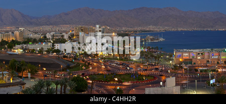 A 3 picture stitch panoramic view of the hotel and beach area of Eilat in the evening with the lights of Aqaba in - Stock Photo