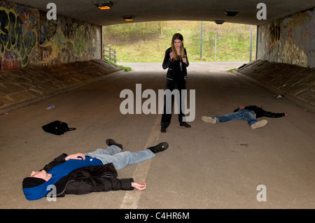 Scene showing young Caucasian woman after defending herself against two male attackers having fought off muggers - Stock Photo