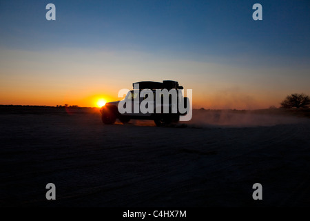 Off Road Vehicle at Sunset in Nxai Pan National Park, Botswana - Stock Photo