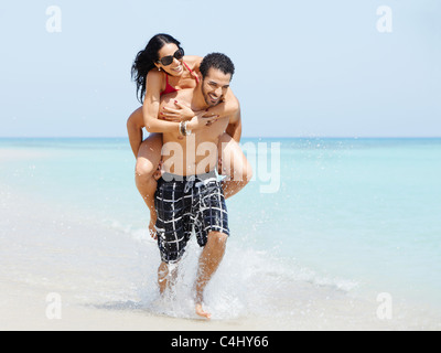 happy maried adult couple having fun and playing on the sea shore in cuba. Horizontal shape, full length, copy space - Stock Photo