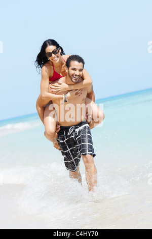 happy maried adult couple having fun and playing on the sea shore in cuba. Vertical shape, full length, copy space - Stock Photo