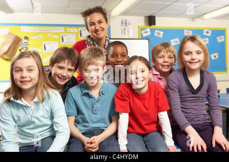 Schoolchildren In classroom with teacher - Stock Photo