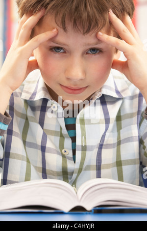 Stressed Schoolboy Studying In Classroom - Stock Photo