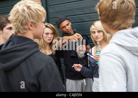Group Of Threatening Teenagers Hanging Out Together Outside Drin - Stock Photo