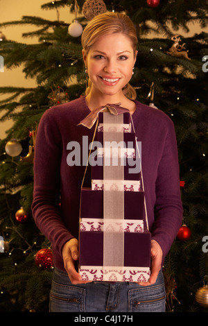 Woman Holding Christmas Gifts In Front Of Tree - Stock Photo