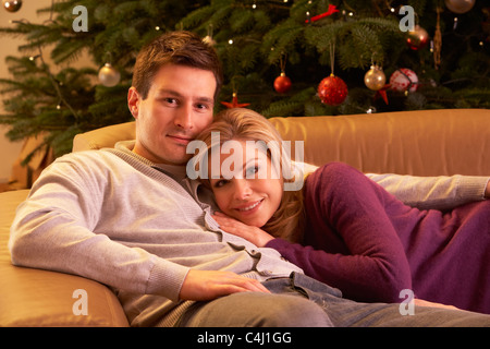 Couple Relaxing In Front Of Christmas Tree - Stock Photo