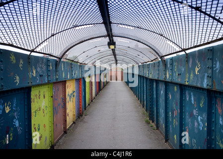 covered urban bridge over railway tracks with graffiti - Stock Photo