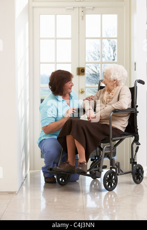 Carer With Disabled Senior Woman Sitting In Wheelchair - Stock Photo
