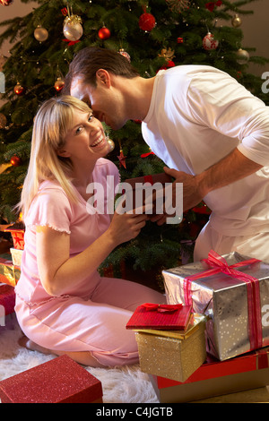 Couple Exchanging Presents In Front Of Tree - Stock Photo