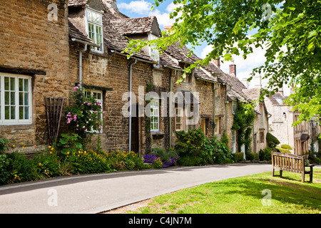 Row of pretty Cotswold stone cottages in the tourist town of Burford, Oxfordshire, England, UK - Stock Photo