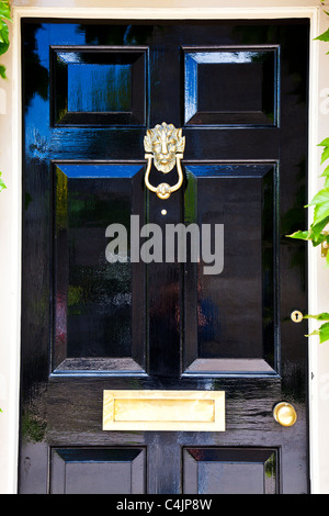 A shiny high gloss black painted front door with highly polished brass door furniture. - Stock Photo