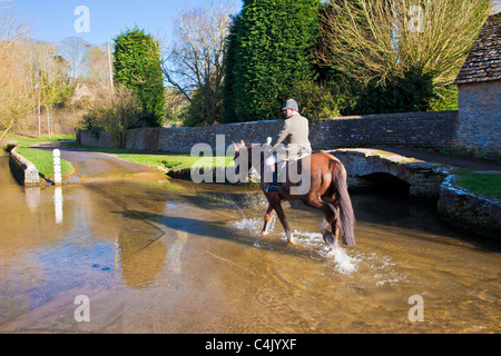 A horse and rider crossing ford in pretty Cotswold village of Shilton, Oxfordshire, England, UK on a sunny day in - Stock Photo