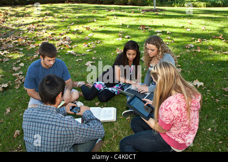 Multi ethnic Ethnically diverse discussion  group  teens study together using mobile phone iPhone iPad devices. MR © Myrleen Pearson
