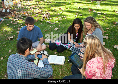 15-18 year years old discussion Multi ethnic group Teens study together using mobile phone iPad iPad laptop devices. - Stock Photo