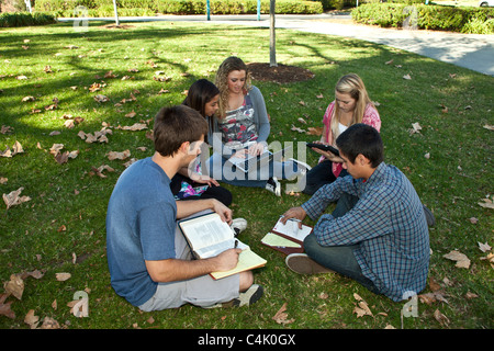 Multi ethnic racial minority Ethnically diverse discussion group teens study together using mobile phone iPhone iPad  devices. MR © Myrleen Pearson