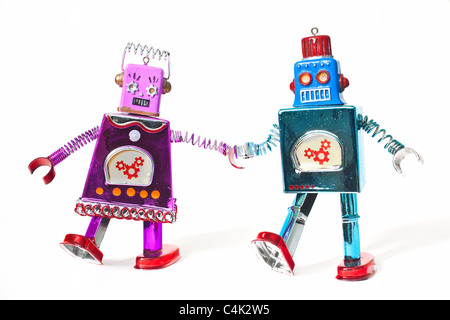 Toy robots holding hands and walking as a couple. - Stock Photo