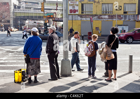people waiting to cross street on spring day at corner of 42nd street & 9th Avenue New York City - Stock Photo