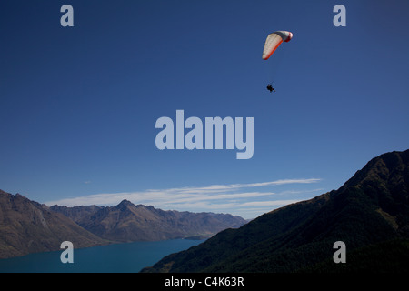 Paragliders flying over Queenstown and lake Wakatipu showing the Remarkables mountain ranges. - Stock Photo
